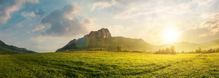 panorama of romania countryside at sunset in evening light. beautiful scenery with trees in haze on a grassy field. huge rocky cliff above the forested hill in the distance. discover romania Stock Photo - 119823588
