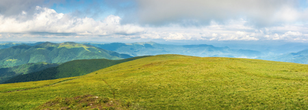 panorama of a mountain landscape in summer. beautiful scenery with low hanging clouds. huge grassy alpine meadow. dividing mountain ridge in the distance. location runa, ukraine Stock Photo