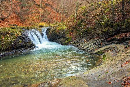 small forest waterfall in autumn. beautiful nature scenery on the river with rocky shore. clear water, fallen foliage and moss on the boulders
