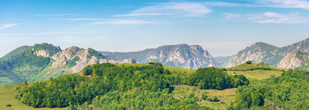 panorama of a landscape with rocky ridge. forested hill in front. wonderful springtime scenery. calm weather with blue sky Фото со стока
