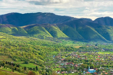 mountainous countryside in springtime. village in the valley, mountain ridge with spots of snow. sunny weather with cloudy sky. view from the hill. beautiful suburb scenery Stock Photo