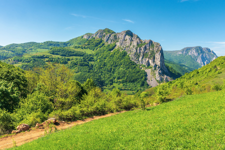 springtime in alba country, romania. wonderful sunny day in mountainous countryside. grassy hillside and gorge with cliffs in the distance under the clear blue sky