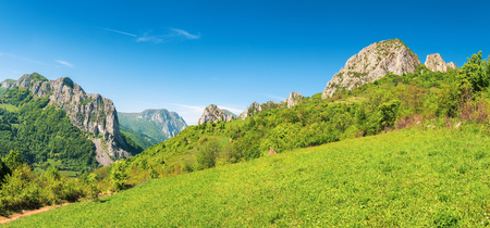 beautiful panorama of romania countryside. wonderful sunny day in mountains. grassy meadow on the hillside and canyon with hanging cliffs in the distance