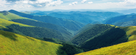 panorama of rolling hills of the ridge in summer. valley down below. grassy alpine slopes. sunny weather Stock Photo