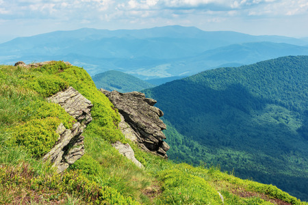 beautiful summer mountain landscape. stunning view from the edge of a hill with huge rock. grassy slopes. ridge and valley in the far distance. sunny weather with cloudy sky at high noon