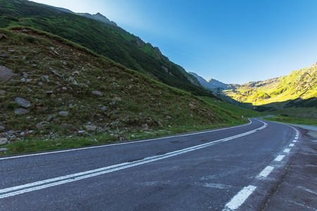 transfagarasan road at sunrise. popular travel destination of romania. beautiful summer landscape in mountains. road winding uphill through gorge with steep rocky cliffs Stock Photo