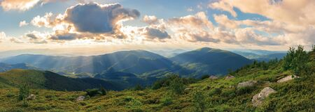 panorama of a gorgeous summer sunset in mountains. sun behind the fluffy clouds. rocks among grassy hills. Stock Photo