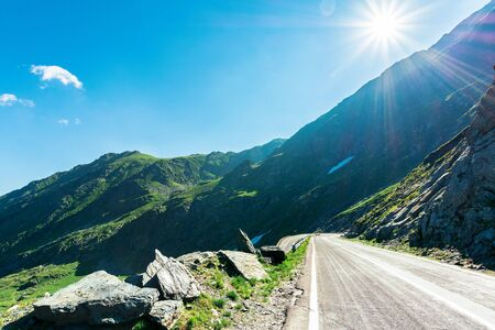 transfagarasan road though mountains. wonderful sunny forenoon weather. rocky slopes and grassy hills. beautiful travel destination. discover romania concept