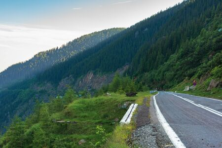 transfagarasan road at sunrise. popular travel destination of romania. beautiful summer landscape in mountains. road winding through gorge with steep rocky cliffs Stock Photo