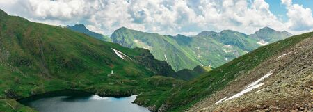 panorama of a fagaras mountains in summer. lake between the hills. beautiful scenery of romania. wonderful destination for a weekend vacation