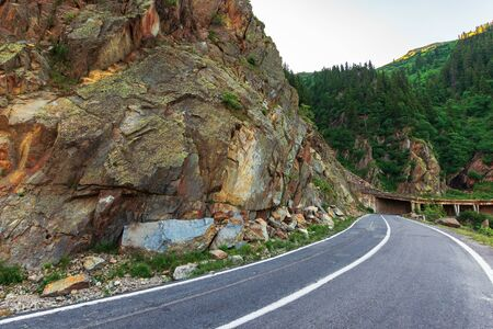 transfagarasan road at sunrise. popular travel destination of romania. beautiful summer landscape in mountains. road winding uphill through gorge with steep rocky cliffs Stockfoto