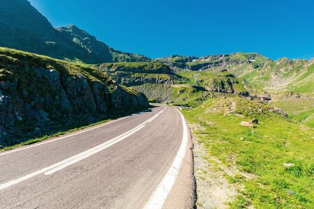 transfagarasan road through mountains. wonderful sunny forenoon weather. rocky slopes and grassy hills. beautiful travel destination. discover romania concept Stock Photo - 127959363