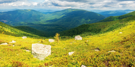 rocks on the grassy hill. beautiful summer panorama in mountains. cloudy sky above the ridge. wonderful nature background.