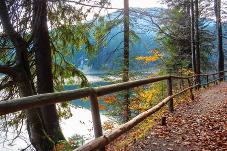Synevyr Bergsee im Herbstabend. schöne Naturlandschaft der Karpaten. gefallenes Laub. Holzzaun entlang des Weges um das Gewässer Standard-Bild