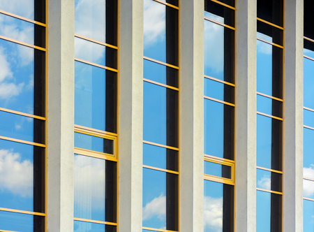 beautiful urban architecture background. window reflection of a clouds on a blue sky. perspective side view with five columns