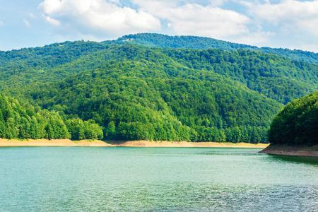 depósito de almacenamiento de agua en las montañas. hermoso paisaje natural en verano. bosque en la orilla alrededor. maravilloso día soleado. ubicación Tereblya Rika HPP