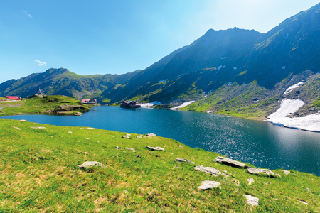 beautiful summer scenery around balea lake. grassy meadows and rocky ridge around. popular travel destination. location fagaras mountains, romania, europe. wonderful sunny weather