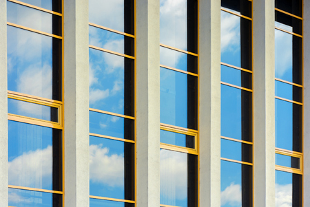 beautiful urban architecture background. window reflection of a clouds on a blue sky. perspective side view with four columns