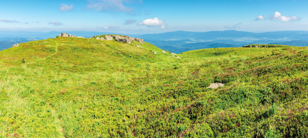 panoramic mountain landscape in summertime. green grassy hills with bunch of rocks in the distance. path through the meadow. sunny weather with fluffy clouds on a blue sky Stock Photo