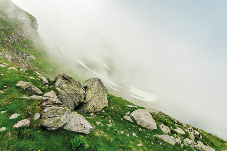 hiking uphill in the fog. huge boulders on a grassy slope. mysterious nature scenery. bad weather condition. extreme tourism concept Stock Photo