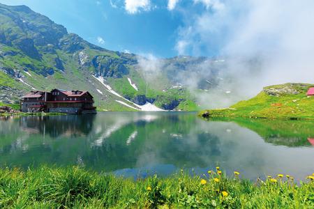 beautiful summer scenery around balea lake. grassy meadows and low clouds around. popular travel destination. location fagaras mountains, romania, europe. wonderful sunny weather Stock Photo