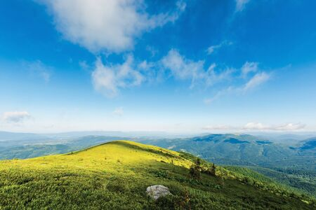 mountain landscape in dappled light. clouds on a blue sky above the green hill and distant ridges. fresh forenoon weather. vivid colors. summer travel and absolute freedom concept
