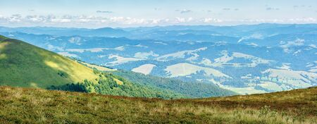 panorama of a mountain landscape. beautiful view in to the valley from the top of a hill. sunny weather with clouds on the sky in summertime