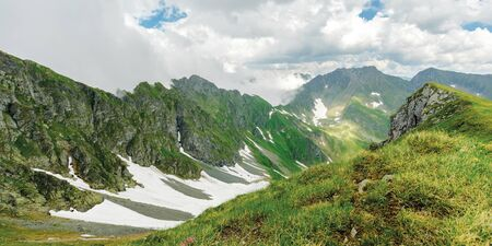 panorama of fagaras mountain ridge in summer. spots of snow on grass of steep slope. rocky tops. cloudy weather. romania landscape Stock Photo