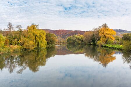 calm water surface of the mountain river in autumn. wonderful carpathian landscape on an overcast day. trees in colorful foliage on the shore. clouds and plants reflection Stock Photo