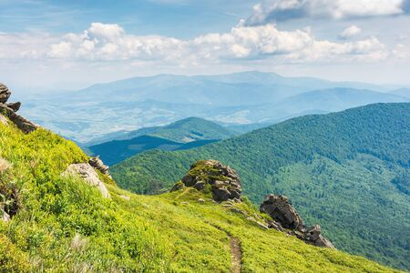 amazing view from the top of a mountain. path through the meadow with huge boulders on the edge. summer landscape with hills of the ridge rolling down in to the mountain. borzhava range on the horizon