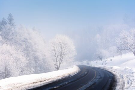road turn in to the forest in winter. amazing foggy weather. trees in hoarfrost. roadside covered with high snow. cold and bright forenoon. deceptive nature beauty concept. keep your eyes on the road message