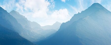 panorama of mountain ridge. bright scenery in afternoon hazy light. sky with fluffy clouds. valley between ridges. beautiful landscape backdrop Stock Photo