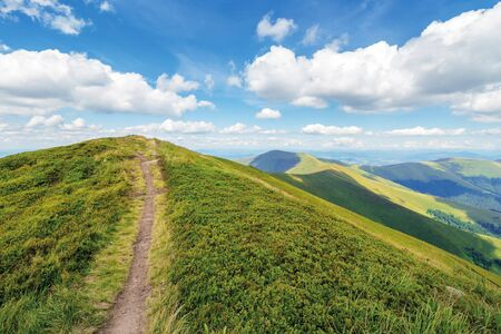 path uphill to the mountain top. beautiful summer scenery with dynamic cloud formations on a blue sky. wonderful landscape with rolling hill of the ridge. Stock Photo