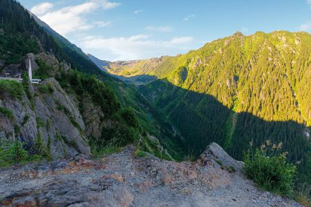 fagaras mountain ridge in the morning. rocky formations in sunlight. beautiful summer scenery. cascada balea in the valley