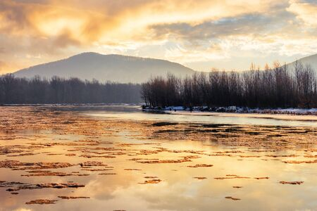 river in mountain at winter sunset. floating melting ice. cloudy sky reflecting in the water surface. wonderful nature scenery Stock Photo