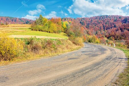old cracked country road in autumn. traditional carpathian countryside. warm sunny day. trees in colorful foliage. green grass on the rural fields. loacrion Uzhok serpentine, ukraine Stock Photo