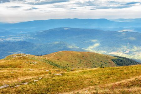 hills and meadows of carpathians in august. beautiful scenery on a cloudy day. boulders among the grass and overcast sky. dappled light in valley. mountain ridge in the distance Stock Photo