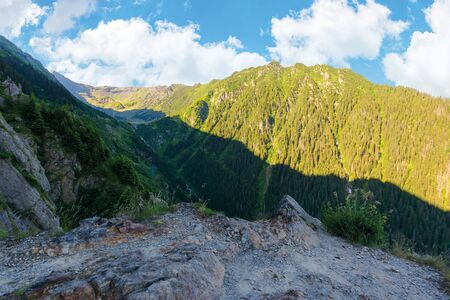valley of the balea stream in fagaras mountains. view from the rocky cliff on a steep slope. forested hillside in the distance. popular travel destination of romania. sunny summer morning Stock Photo