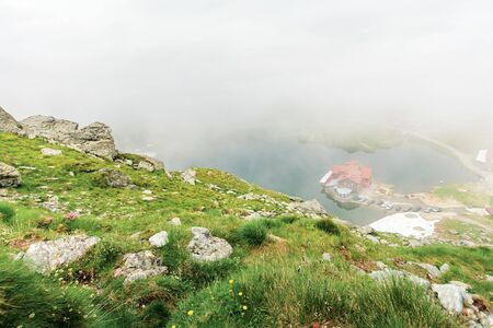 lake balea in dramatic weather. beautiful destination in fagaras mountain of romania. view through clouds from the top of a ridge. steep slopes with rocks among the grass. famous road 7C in the valley