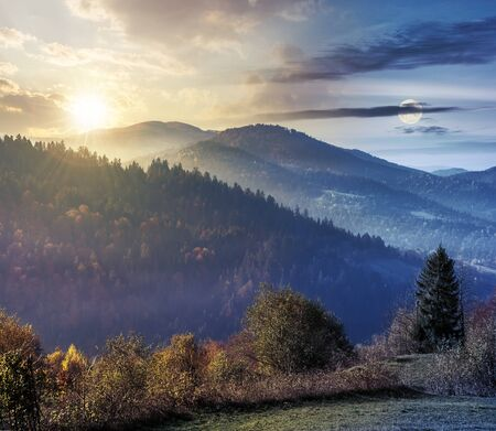 day and night time change concept above countryside in mountains. trees on the edge of a grassy meadow beneath sun and moon. hills rolling in to the distance. hazy weather.