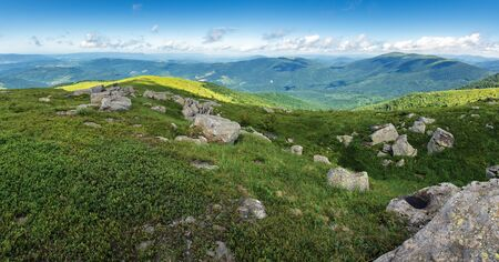 beautiful summer panorama in mountains. grassy meadows, rocks and mountain range in the distance.