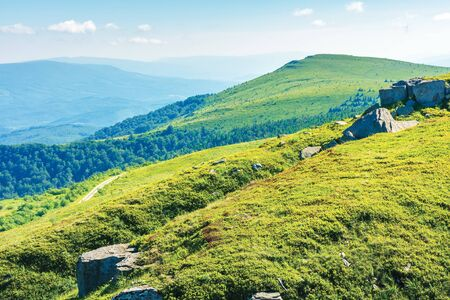 beautiful summer landscape in mountains. grassy meadows, rocks and summit in the distance. ridge in the distance Stock Photo