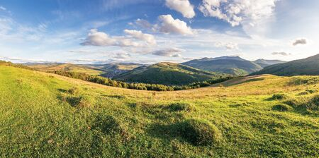panorama of a countryside in mountains. beautiful early autumn landscape in evening light. grassy meadow on the hill. fluffy clouds above the distant ridge. village down in the valley Stock Photo