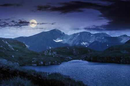 alpine glacier capra of fagaras mountains at night in full moon light. gorgeous summer landscape. good weather with clouds on the sky. rocks on the grassy slopes. popular travel destination of romania