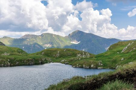 alpine glacier capra of fagaras mountains. gorgeous summer landscape. good weather with clouds on the sky. rocks on the grassy slopes. popular travel destination of romania Stock Photo