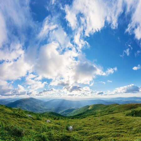 amazing summer landscape at sunset. grassy hills rolling down in to the valley. mountain range in the distance. gorgeous cloudscape on the blue evening sky with light beams. absolute freedom concept Stock Photo