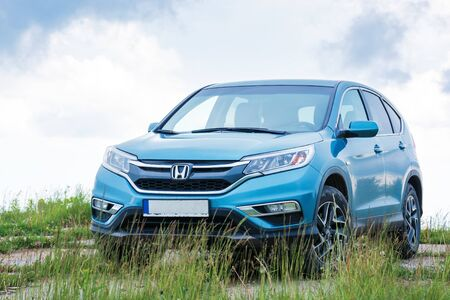 mnt. runa, ukraine - jun 22, 2019: honda crv on a paved platform in mountains. 4 generation of a popular family SUV, restyling model 2015 in cyan blue color. cloudy day and even light