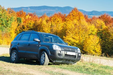 Podobovets, Ukraine - OCT 14, 2018: Hyundai Tucson SUV on the mountain road in autumn. forest in colorful fall foliage near by. ridge in the distance. sunny weather.