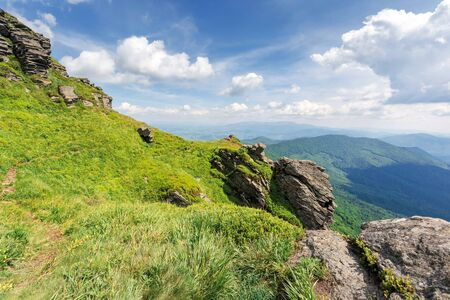 beautiful summer landscape of carpathians. rocks on the grassy slope of a mountain. borzhava ridge in the distance. clouds on the blue sky. location mnt. pikui, transcarpathia, ukraie Stock Photo
