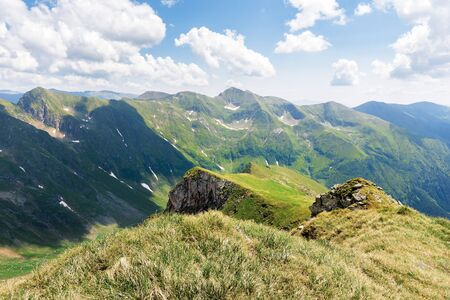 beautiful landscape of fagaras mountains. rocks on steep grassy slopes. snow in the deep valley. wonderful summer weather with clouds on the sky Stock Photo